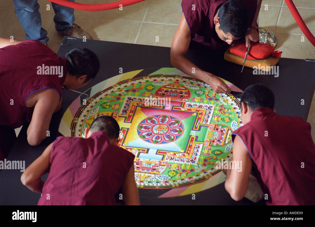 Four monks work on a nearly completed mandala - Stock Image