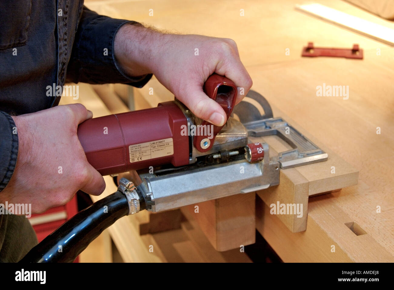 Close Up Of Craftsman In Woodworking Shop Using An Industrial
