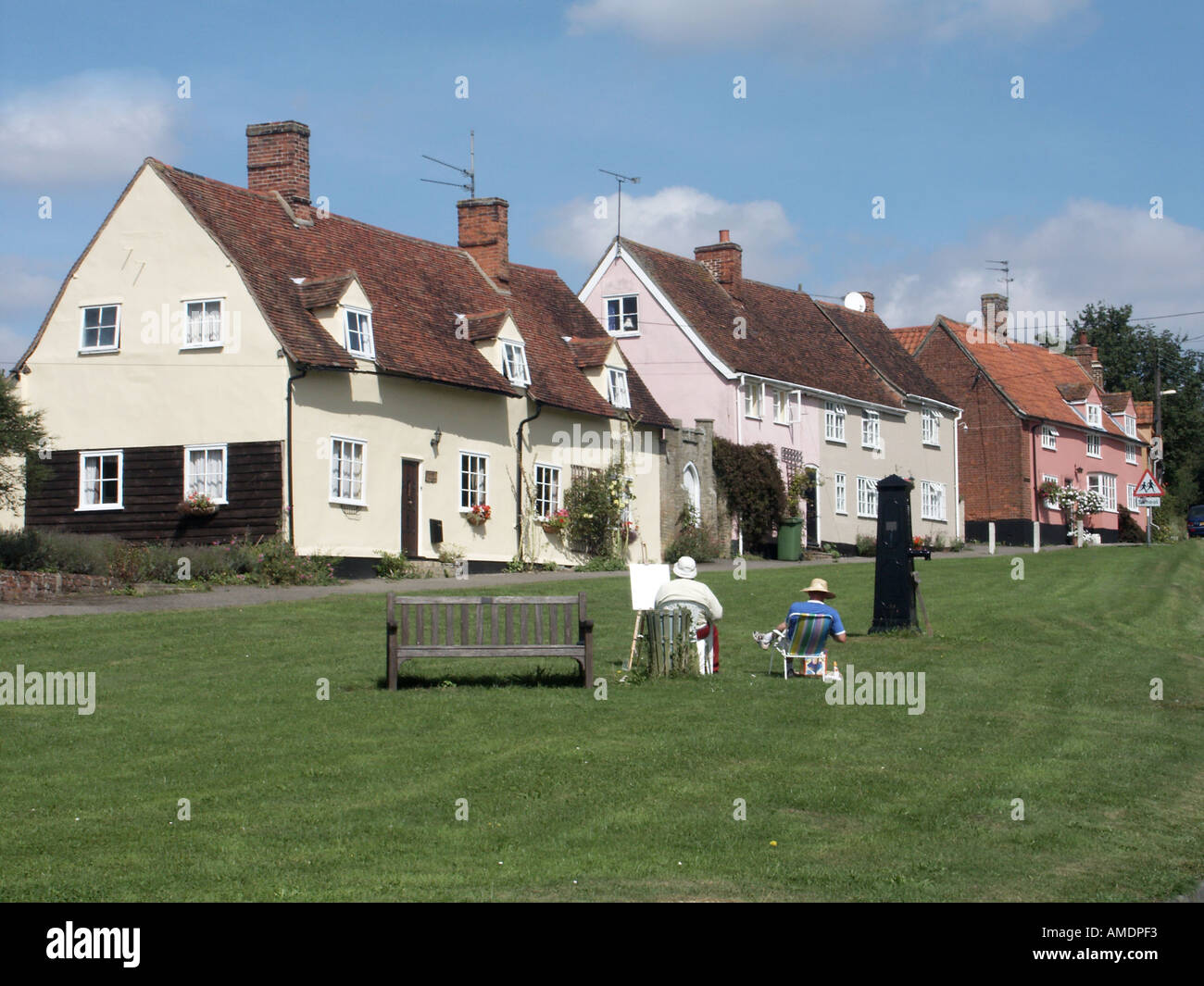 Monks Eleigh village green with cottages people relaxing including an artist - Stock Image
