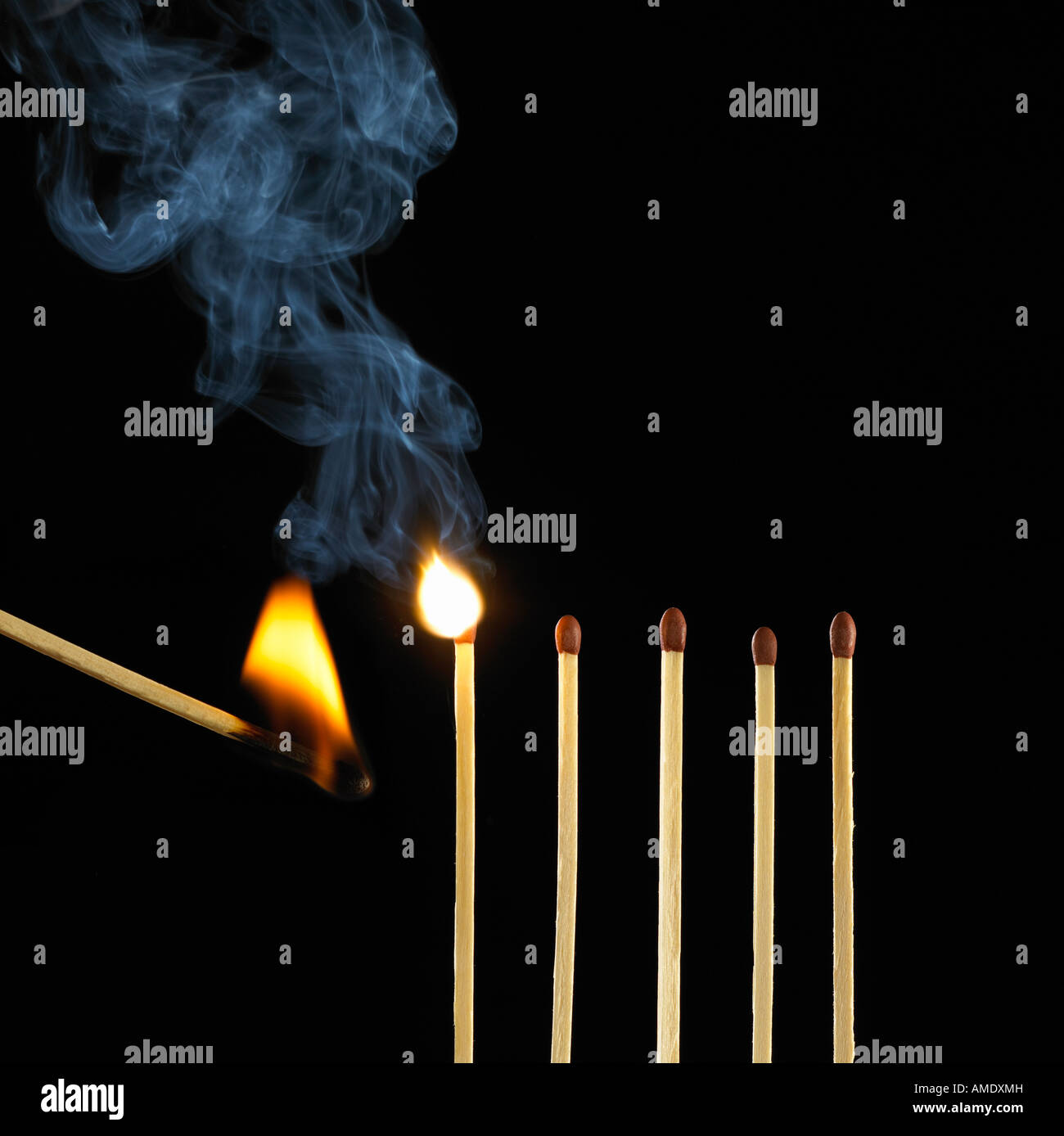BURNING MATCH SETTING FIRE TO ROW OF FIVE MATCHES - Stock Image