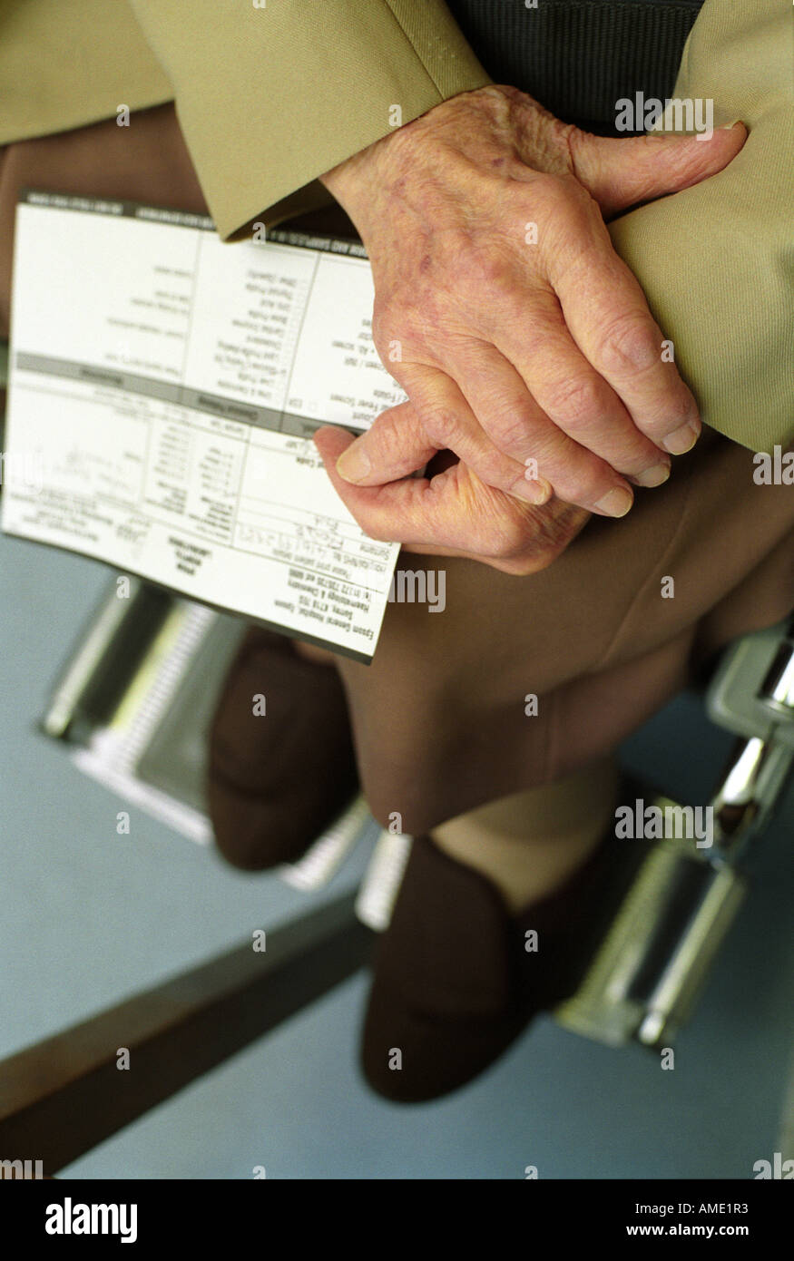 Hands of an elderly patient sitting in a wheelchair holding medical records, health centre, London, UK. - Stock Image
