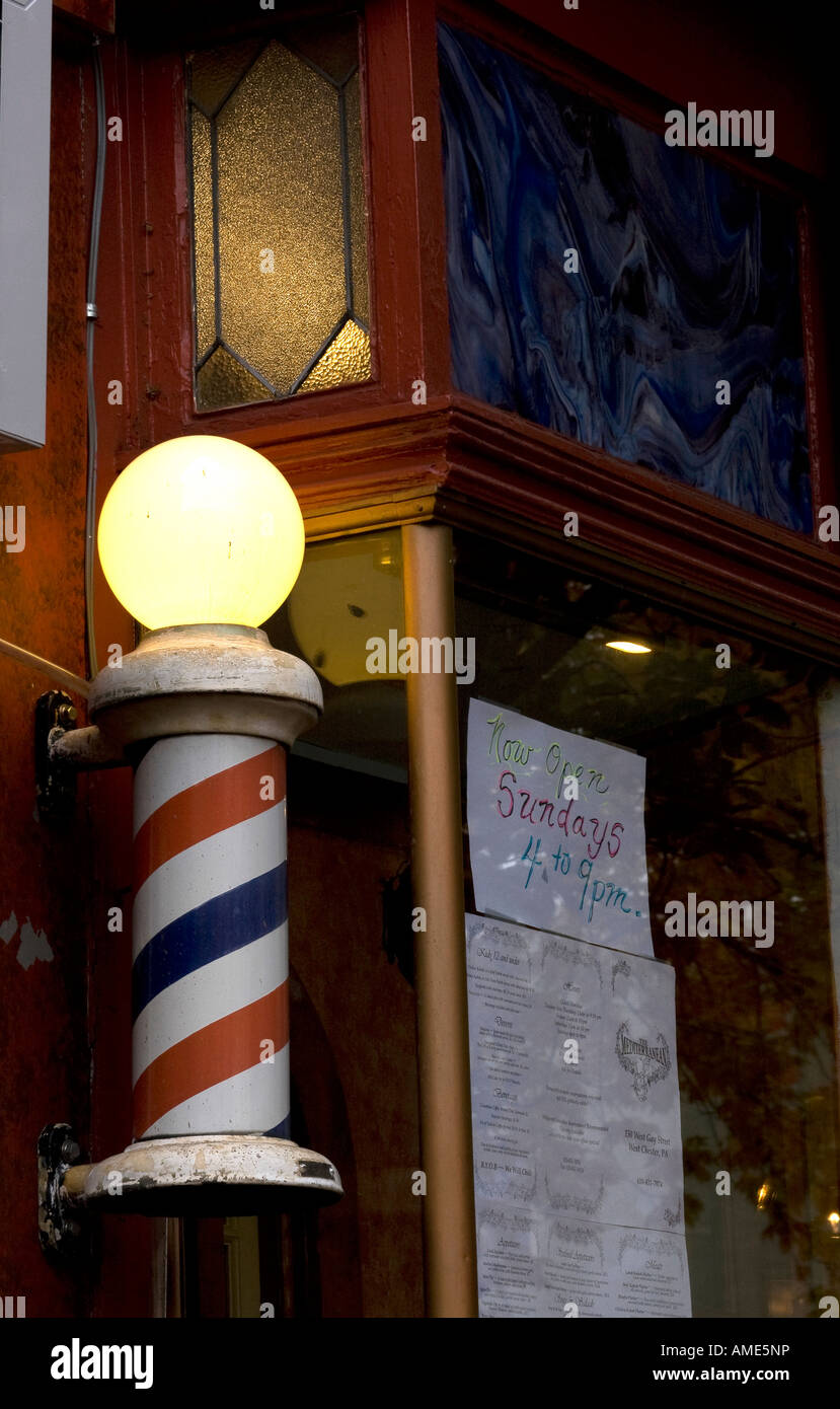 A Barber shop pole spinning in town. - Stock Image