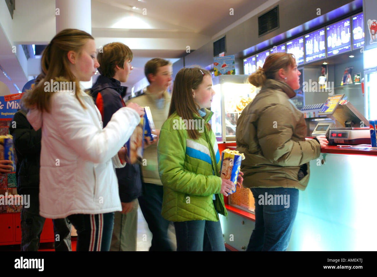 teenagers queuing up to get sweets at a cinema before the film starts - Stock Image