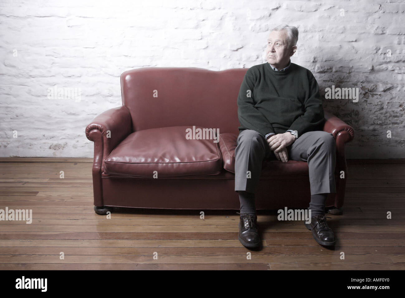 Old Man Seated Down In A Red Sofa An Empty Living Room Desaturated