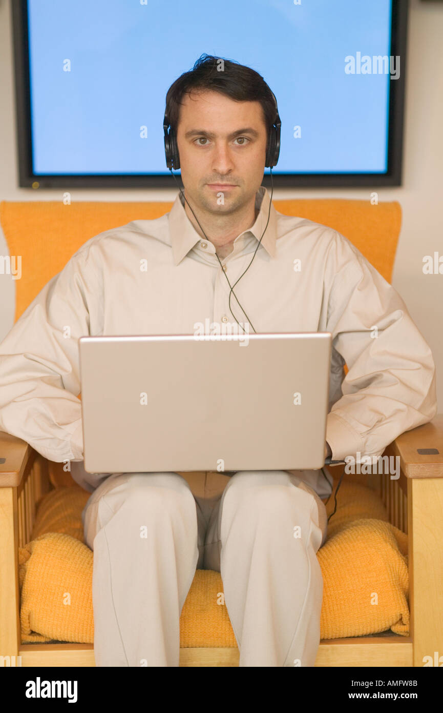 Man using a laptop with plasma screen in background - Stock Image