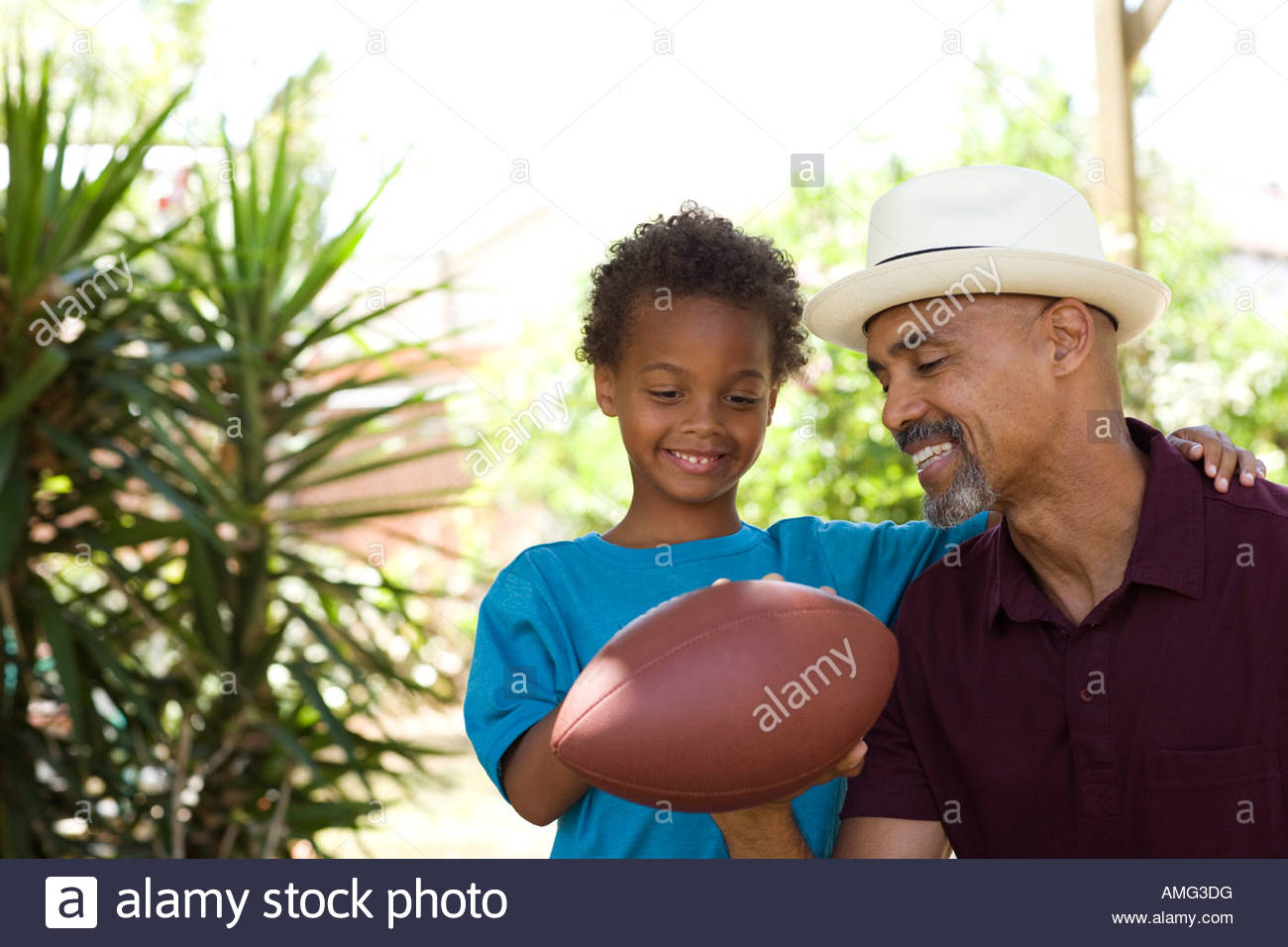 Man and young boy holding a football outdoors - Stock Image