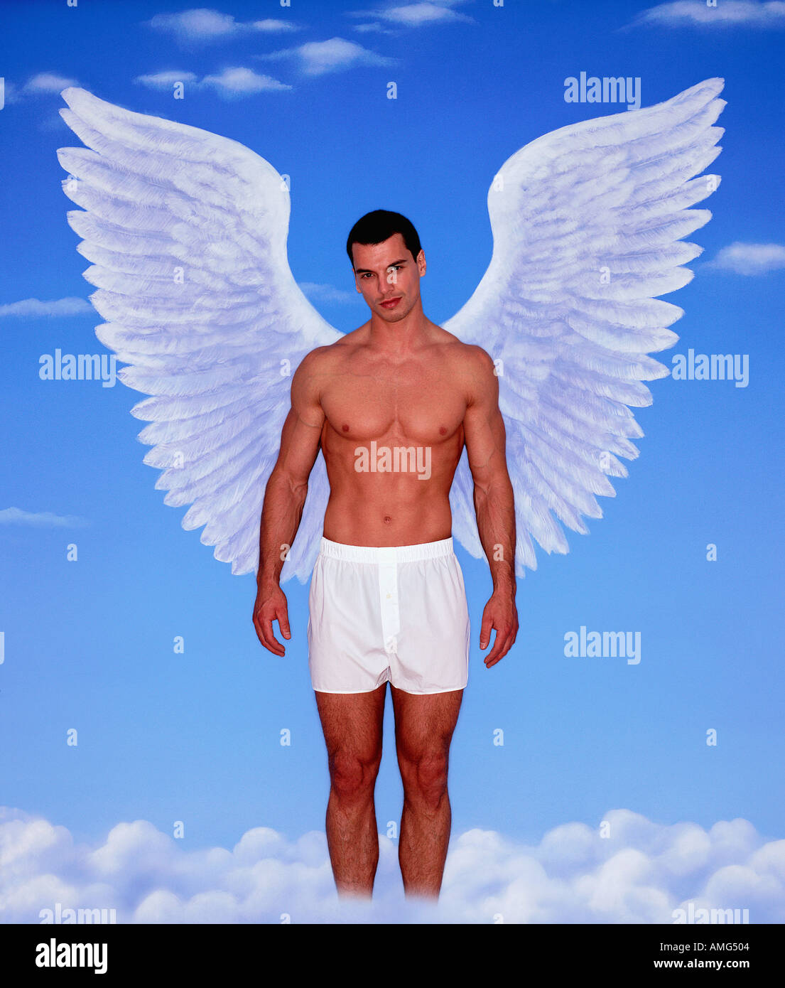 A portrait of a young man in white boxer shorts and wings against blue sky background - Stock Image