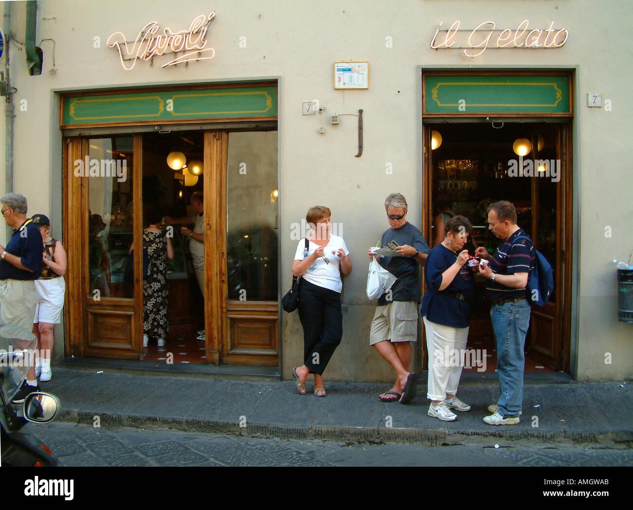 People eating ice creams outside the Vivoli ice cream parlour Florence Italy - Stock Image