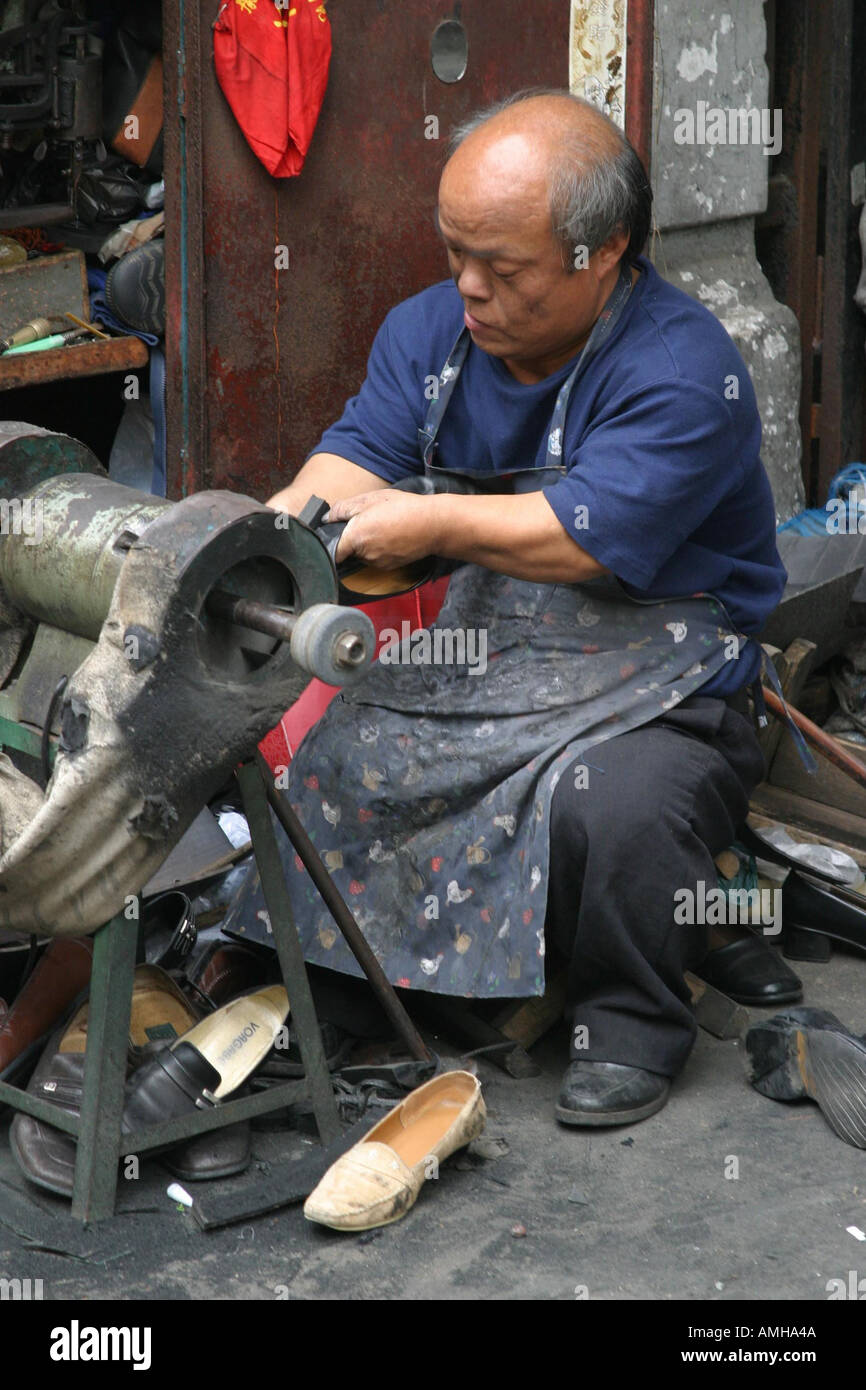 An old man repairs shoes in the street in Shanghai China - Stock Image