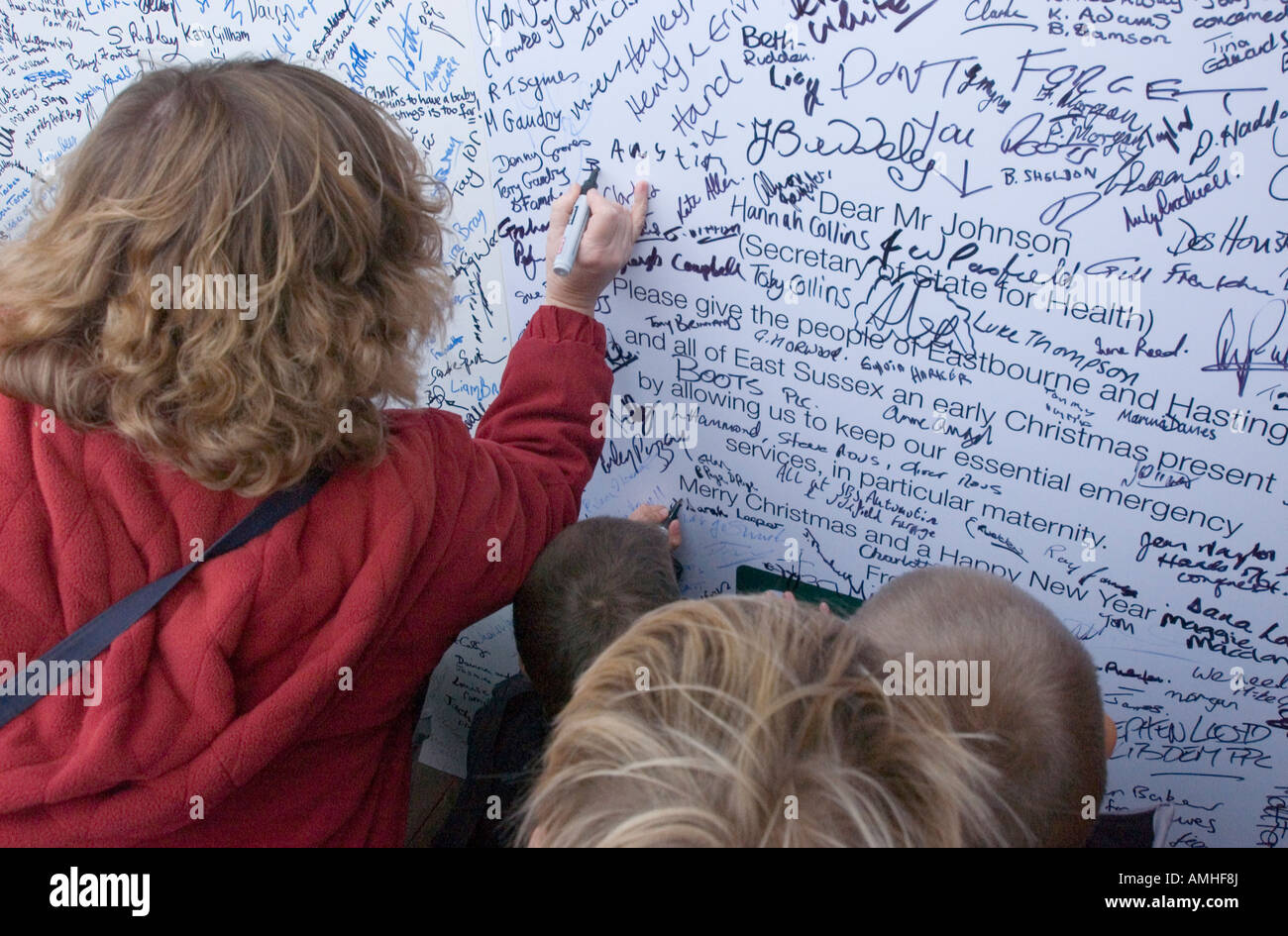 Signing a Christmas card for Alan Johnson, Secretary of State for Health during a rally against downgrading maternity - Stock Image