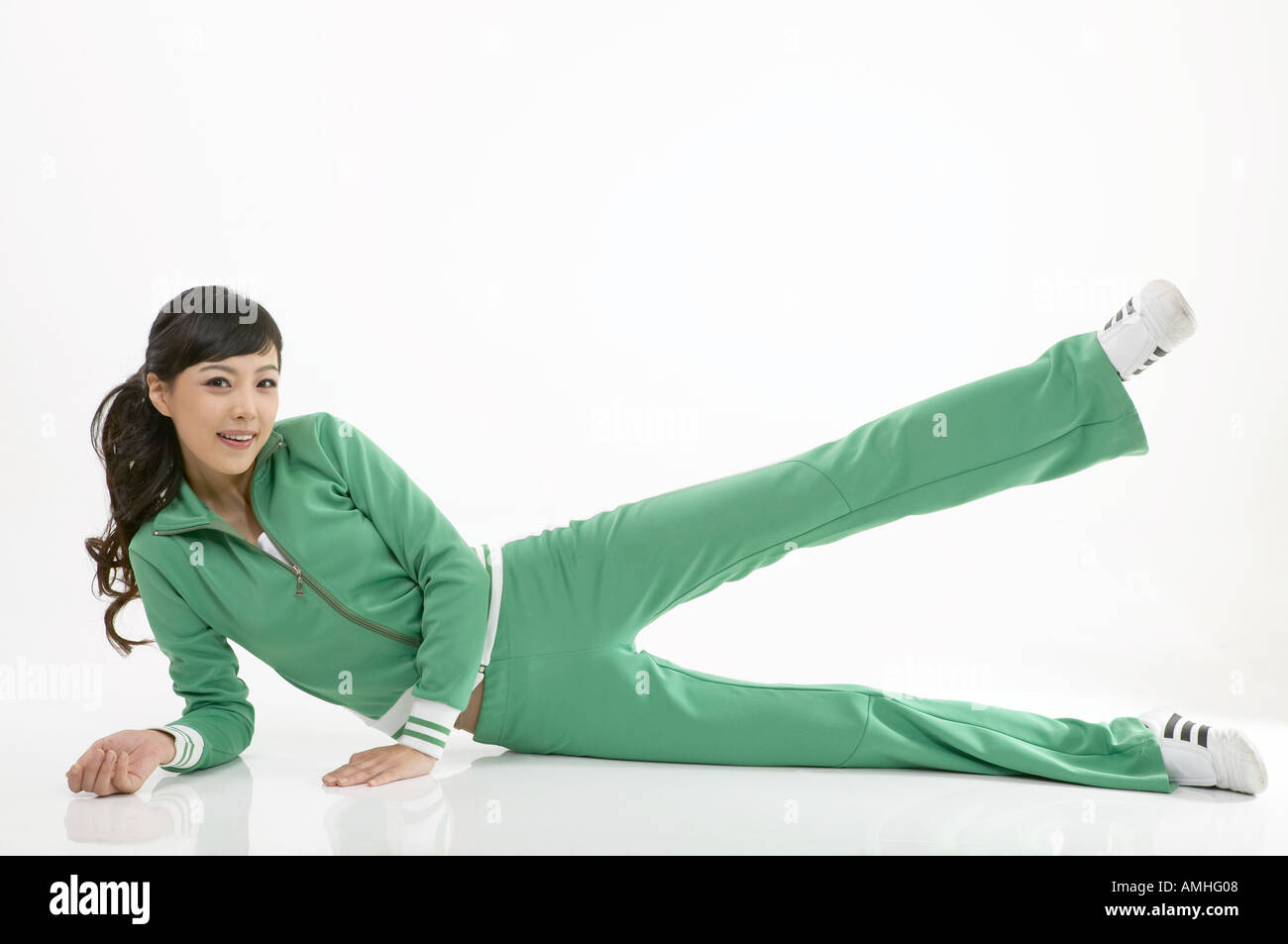 A woman in green gym suit doing leg exercise - Stock Image