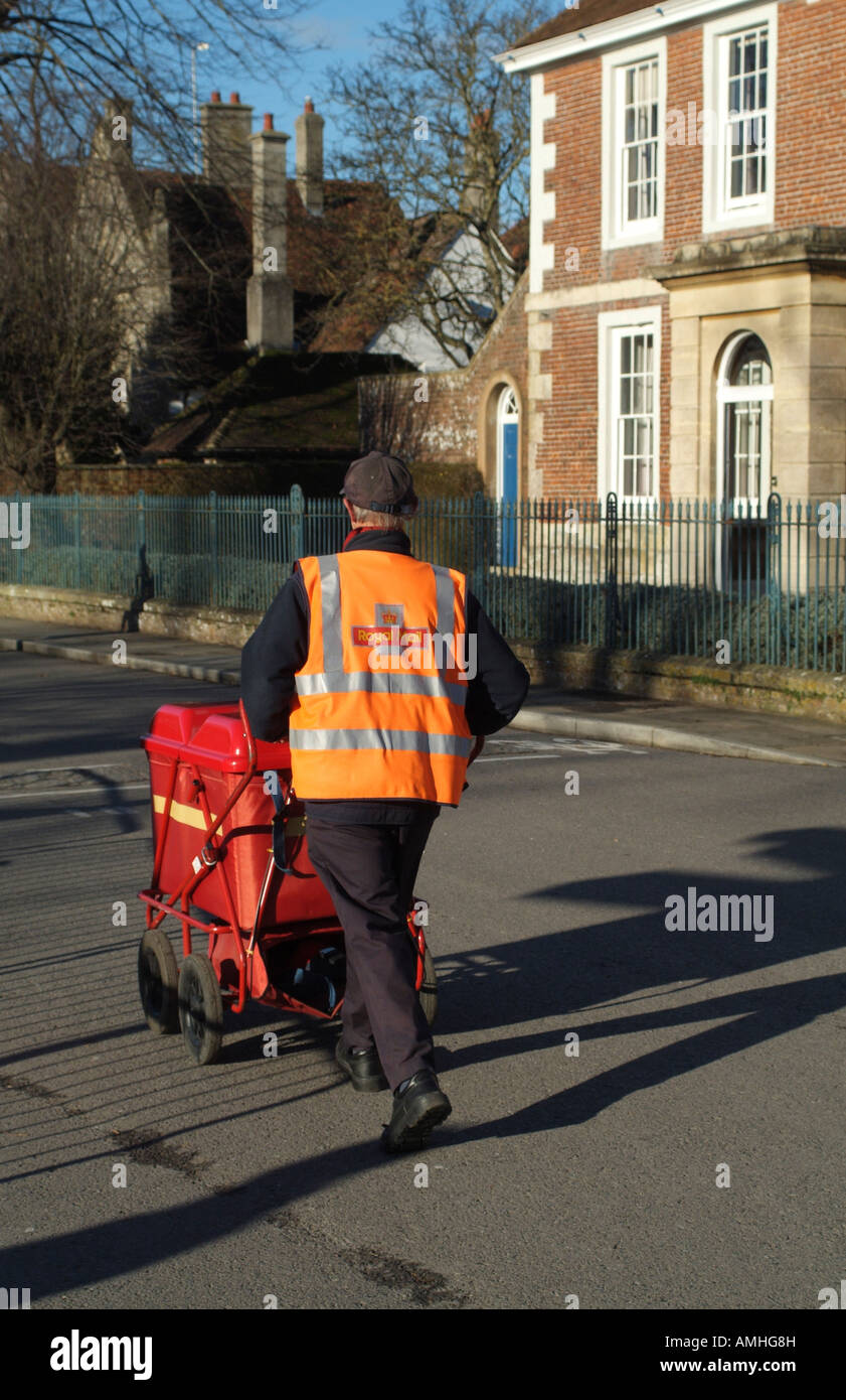 Postman Pushing his Red Trolley Containing Mail on his Delivery Round in Salisbury Wiltshire England UK Stock Photo