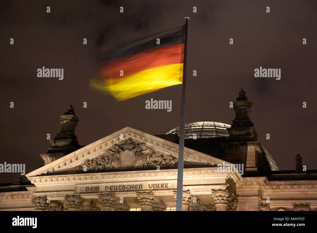 german flag flying fluttering on flagpole outside reichstag building Berlin Germany - Stock Image