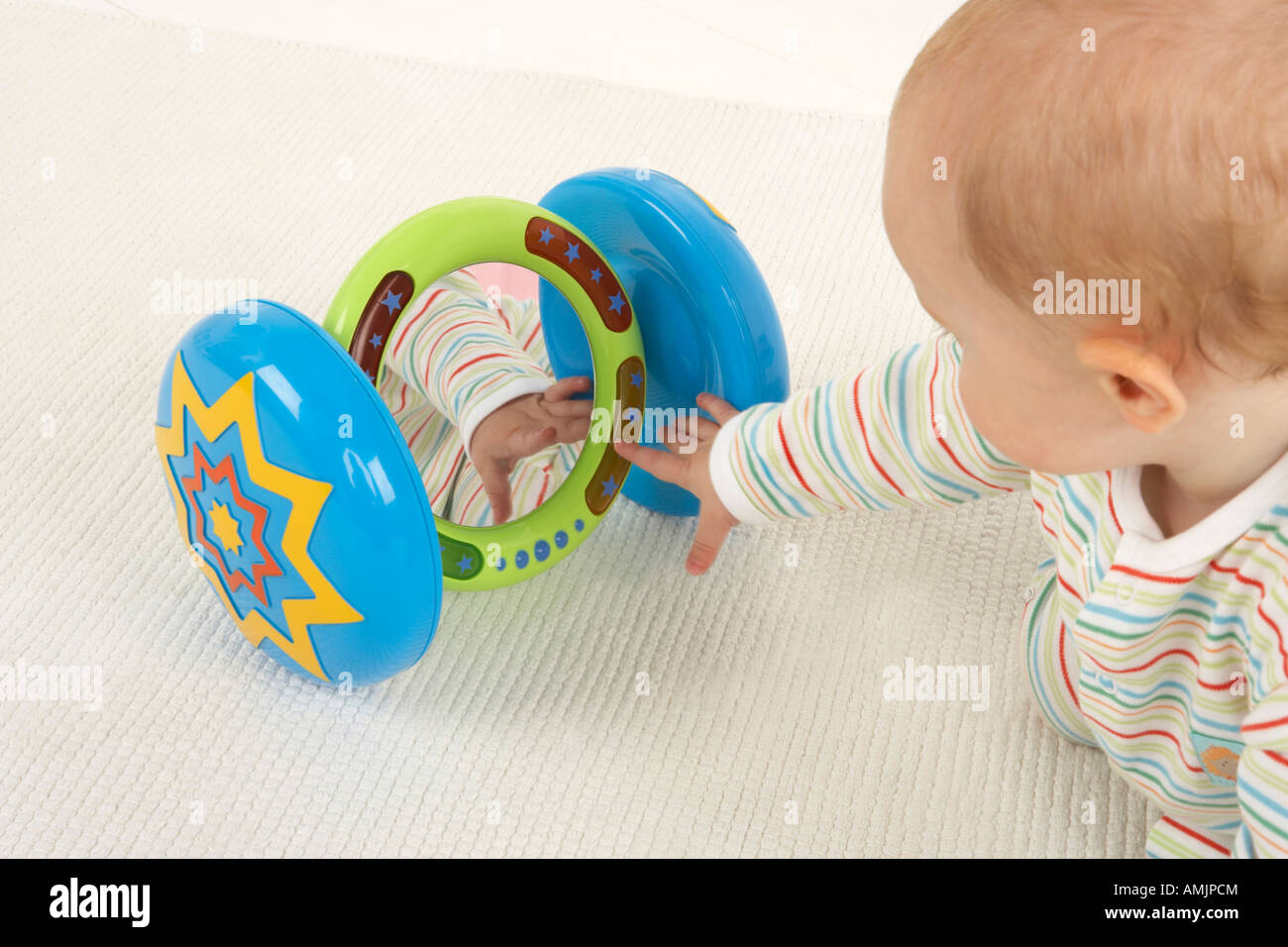 A baby plays on the floor with a mirror on wheels toy Stock Photo ...