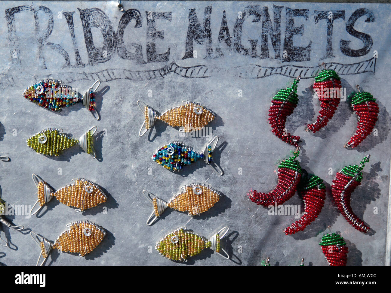 African beaded wire fish and chilli peppers - Stock Image