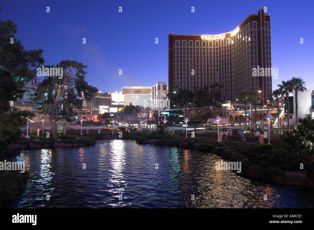 Treasure Island Hotel and Casino with reflections in the lake at dusk on The Strip in Las Vegas Nevada USA - Stock Image