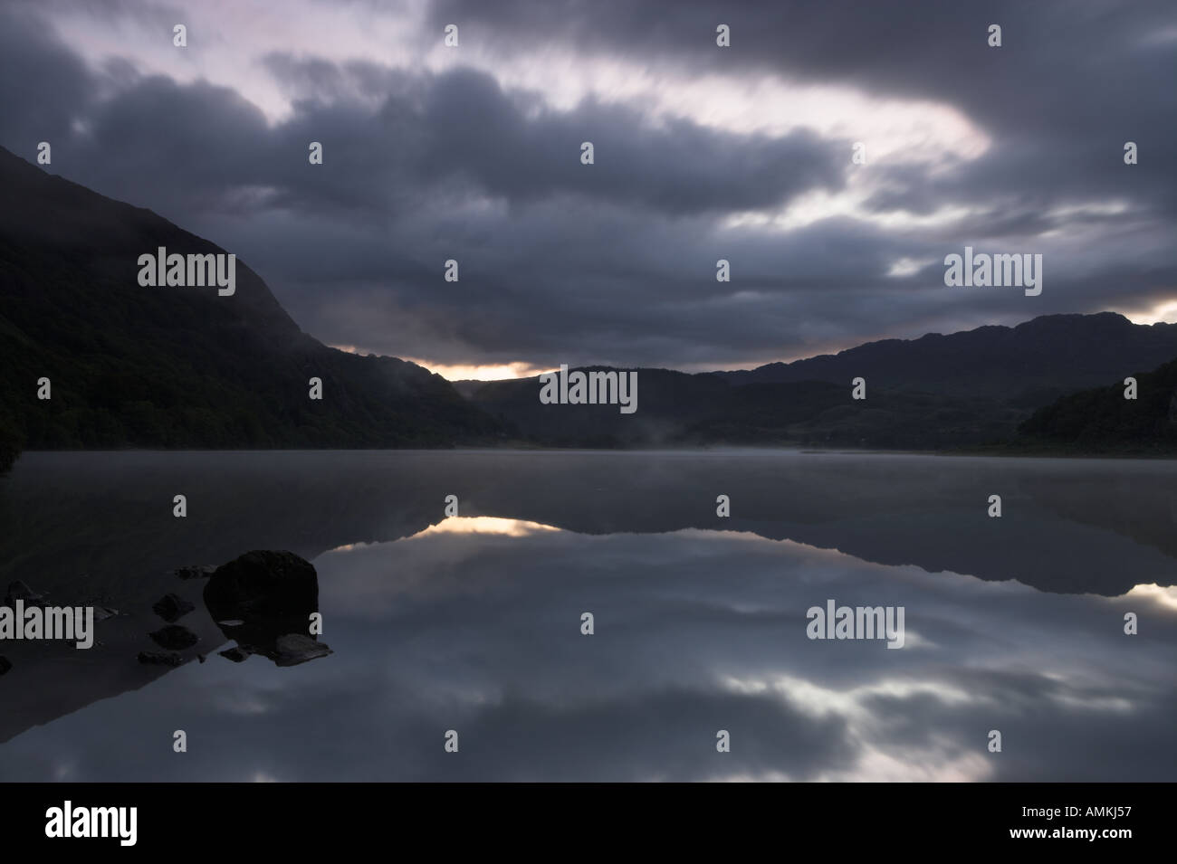 Mirrored Dawn over Llyn Dinas Wales UK Stock Photo