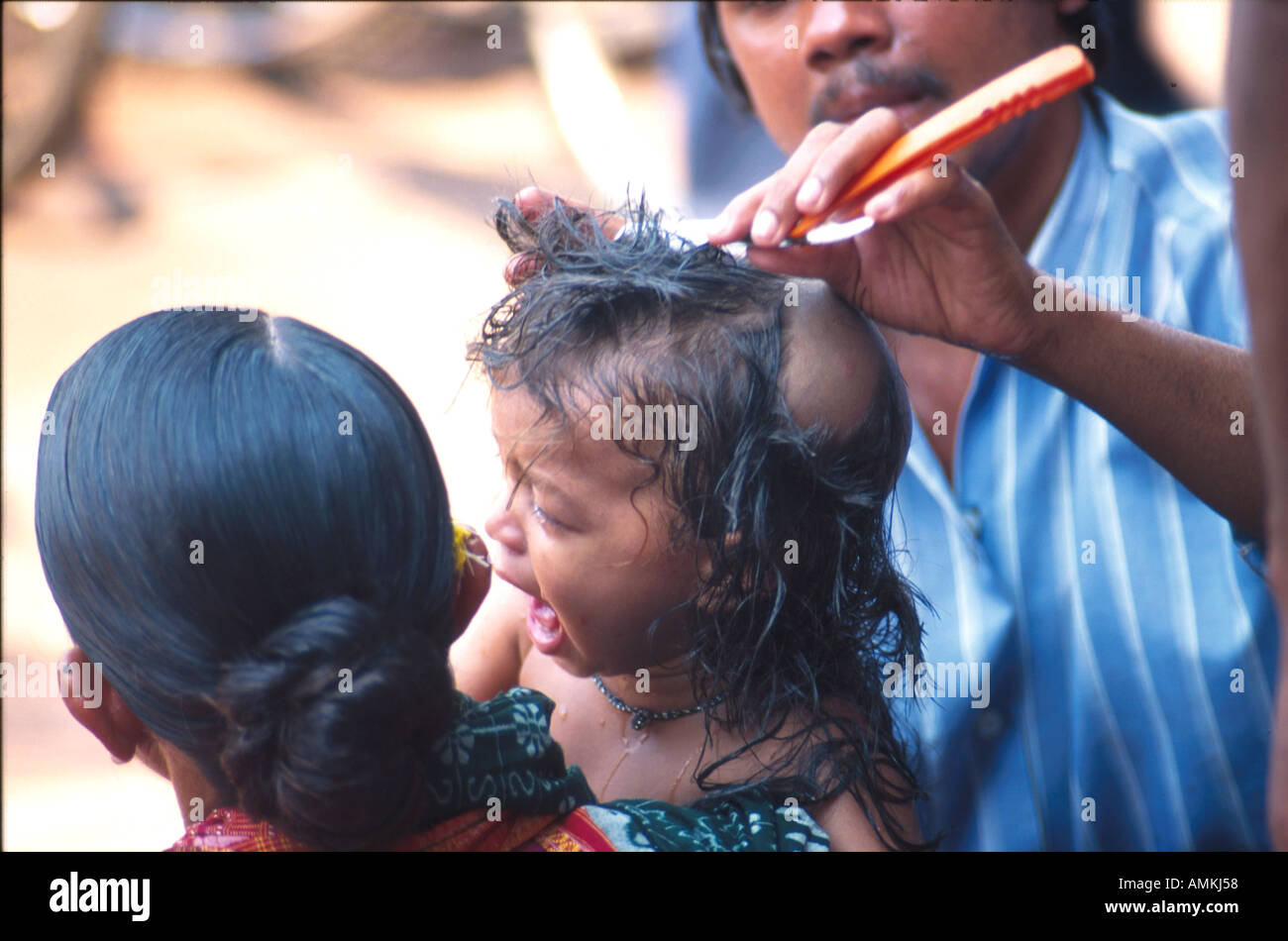 A child cries during Mundan or head shave ceremony by a braber Stock