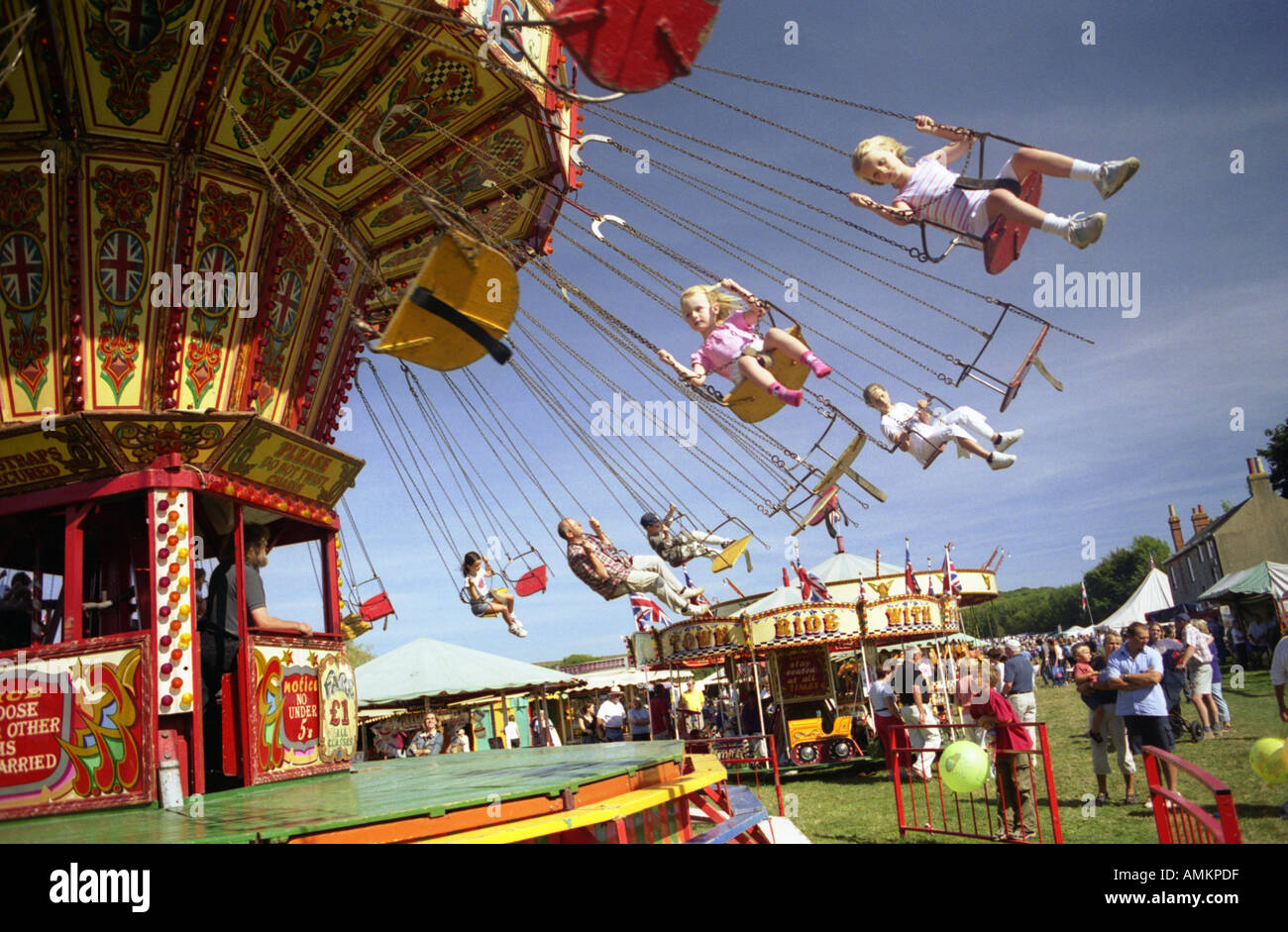 Two girls ride in seats on a carousel. Findon Village Sheep Fair, West Sussex England Stock Photo