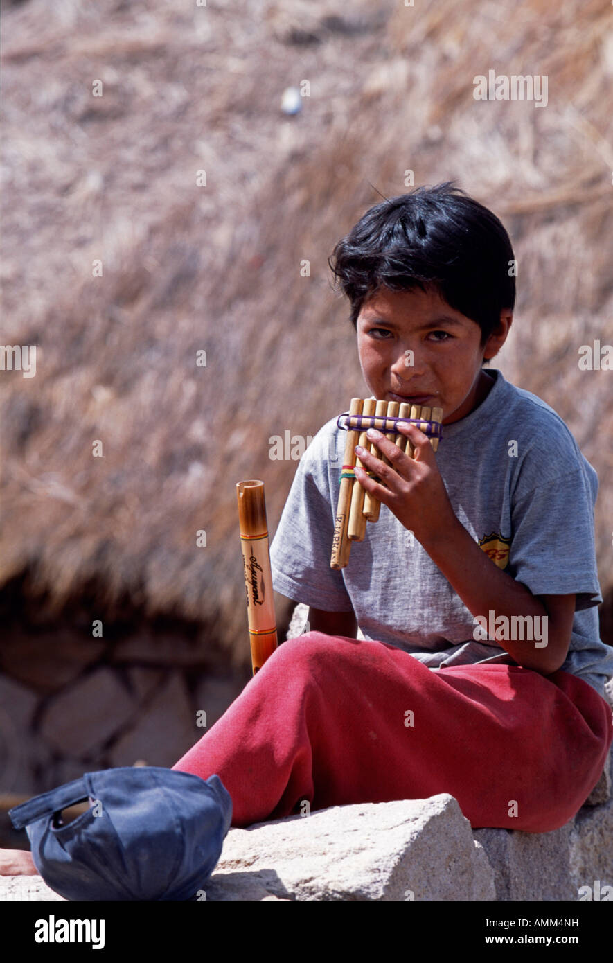 A boy plays the panpipes in the village of San Pedro de Quemez which sits on the southern shore of the Salar de - Stock Image
