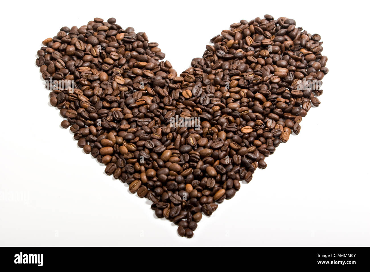 An heart shaped pile of coffee beans isolated on white background - Stock Image