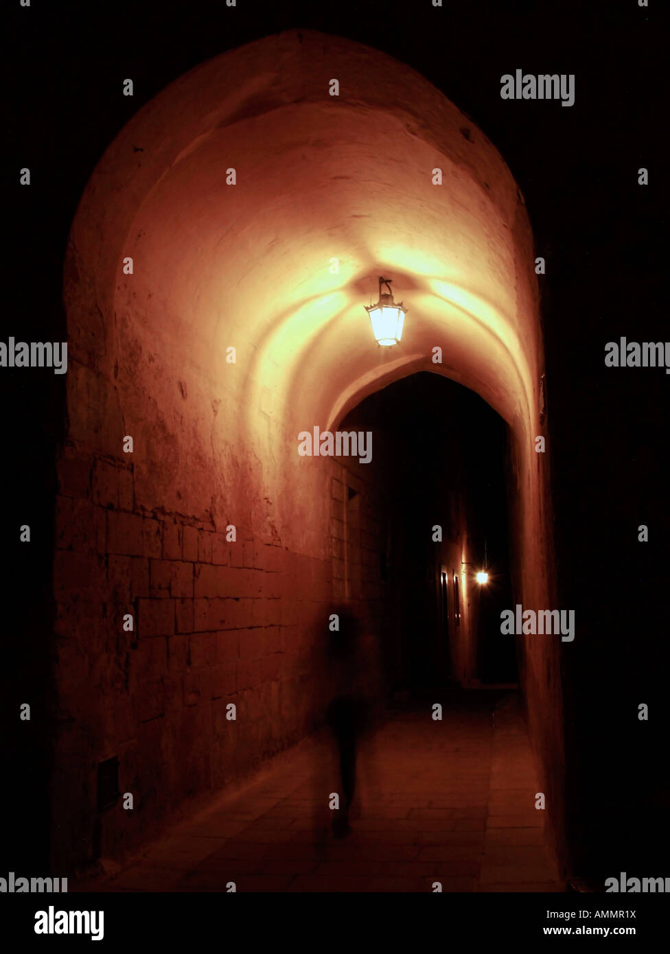 Ghost walking through medieval archway - Stock Image