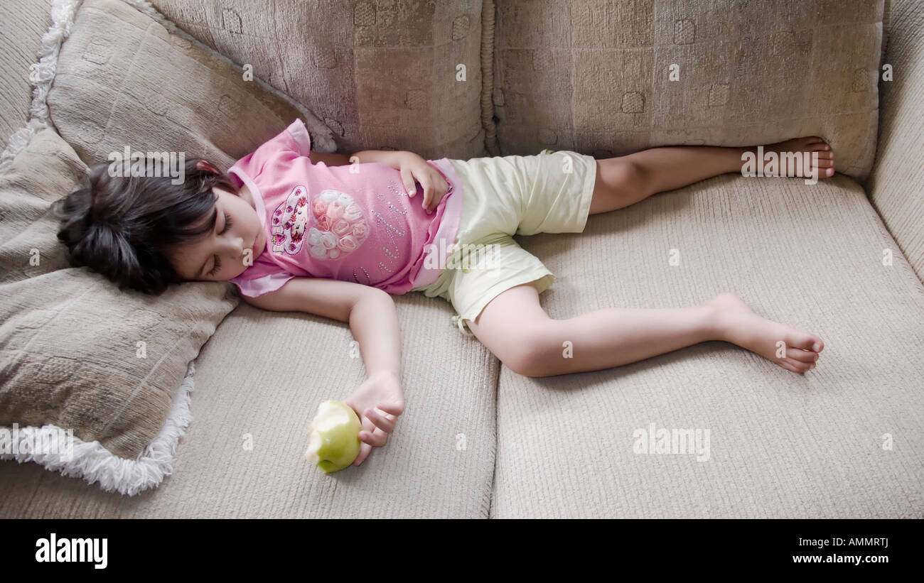 Girl aged four years sleeps on sofa holding half eaten apple - Stock Image