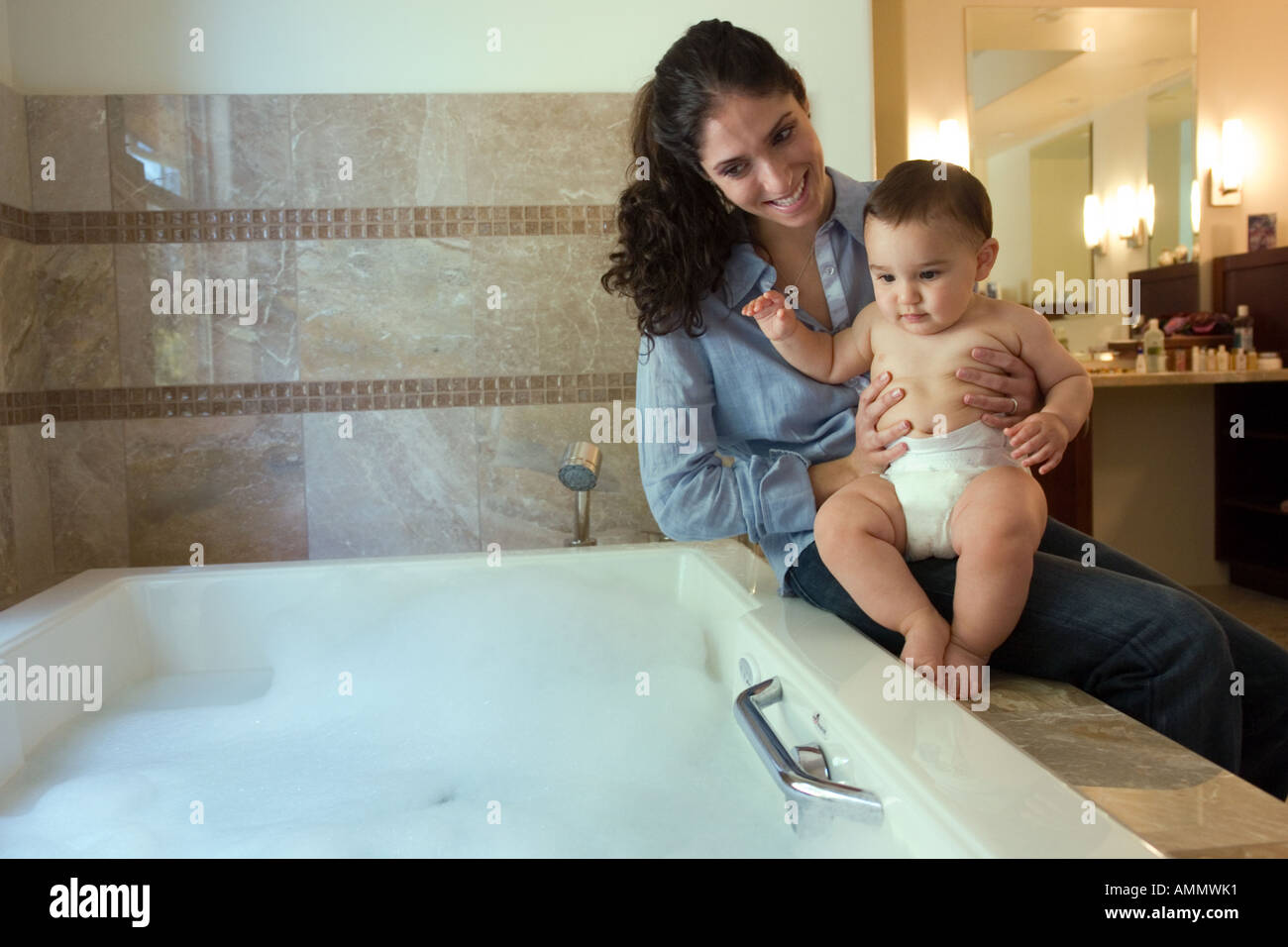 Portrait of a mother about to give baby son a bath Stock Photo ...