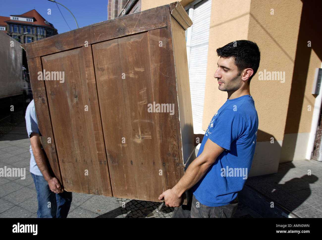 Removal men carrying furniture, Berlin, Germany Stock Photo