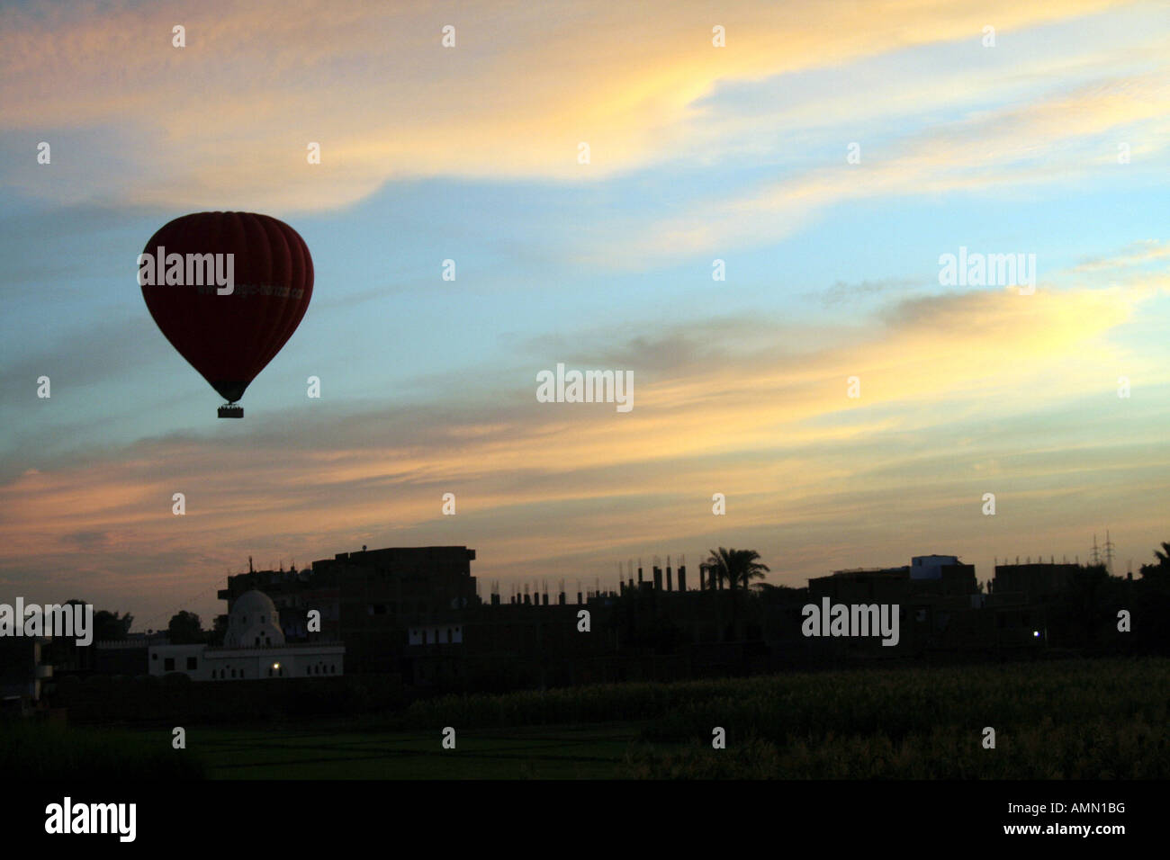 Hot Air Balloon Silhouetted in Front of Beautiful Sunrise [Near Luxor, Egypt, Arab States, Africa].             Stock Photo