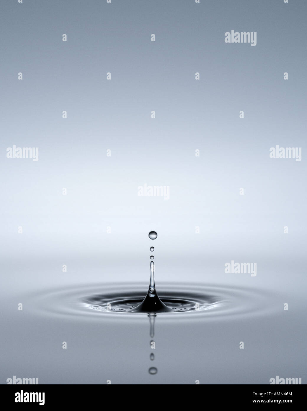 An inverted ripple of water with drops above it - Stock Image