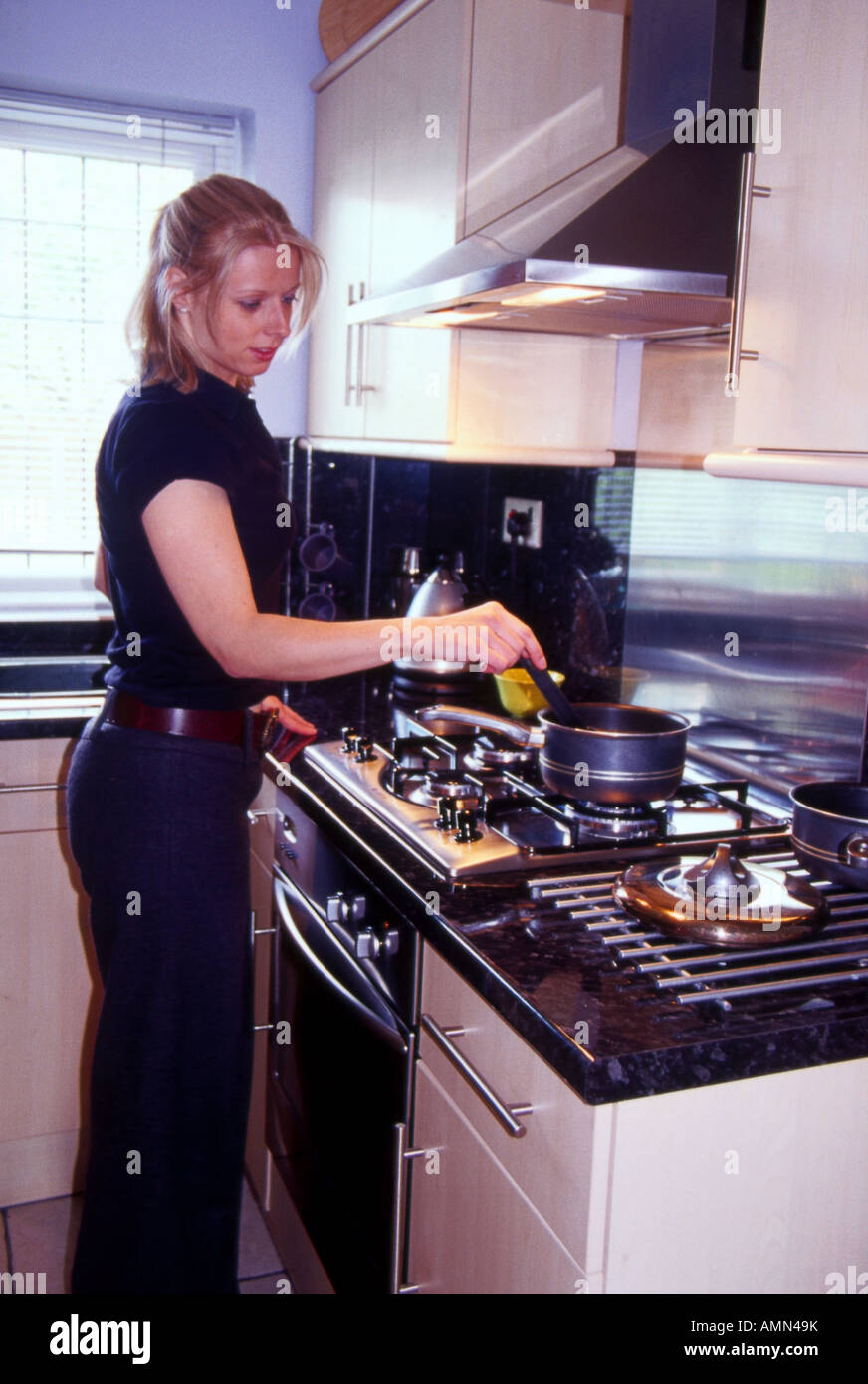 Woman Cooking On Gas Stove Stock Photo Alamy