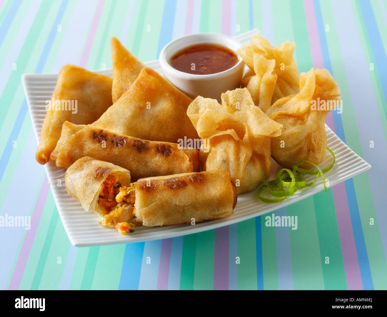 chinese starters deep fried breaded prawns spring rolls dim sum and samosas - Stock Image