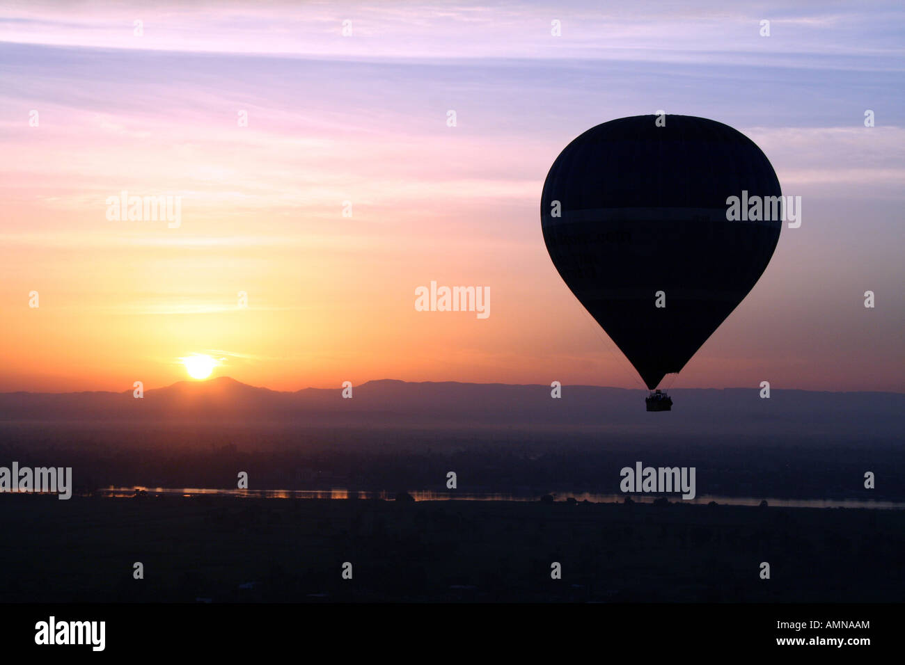 Hot Air Balloon Silhouetted in Front of Beautiful Sunset over the River Nile [Near Luxor, Egypt, Arab States, Africa]. Stock Photo