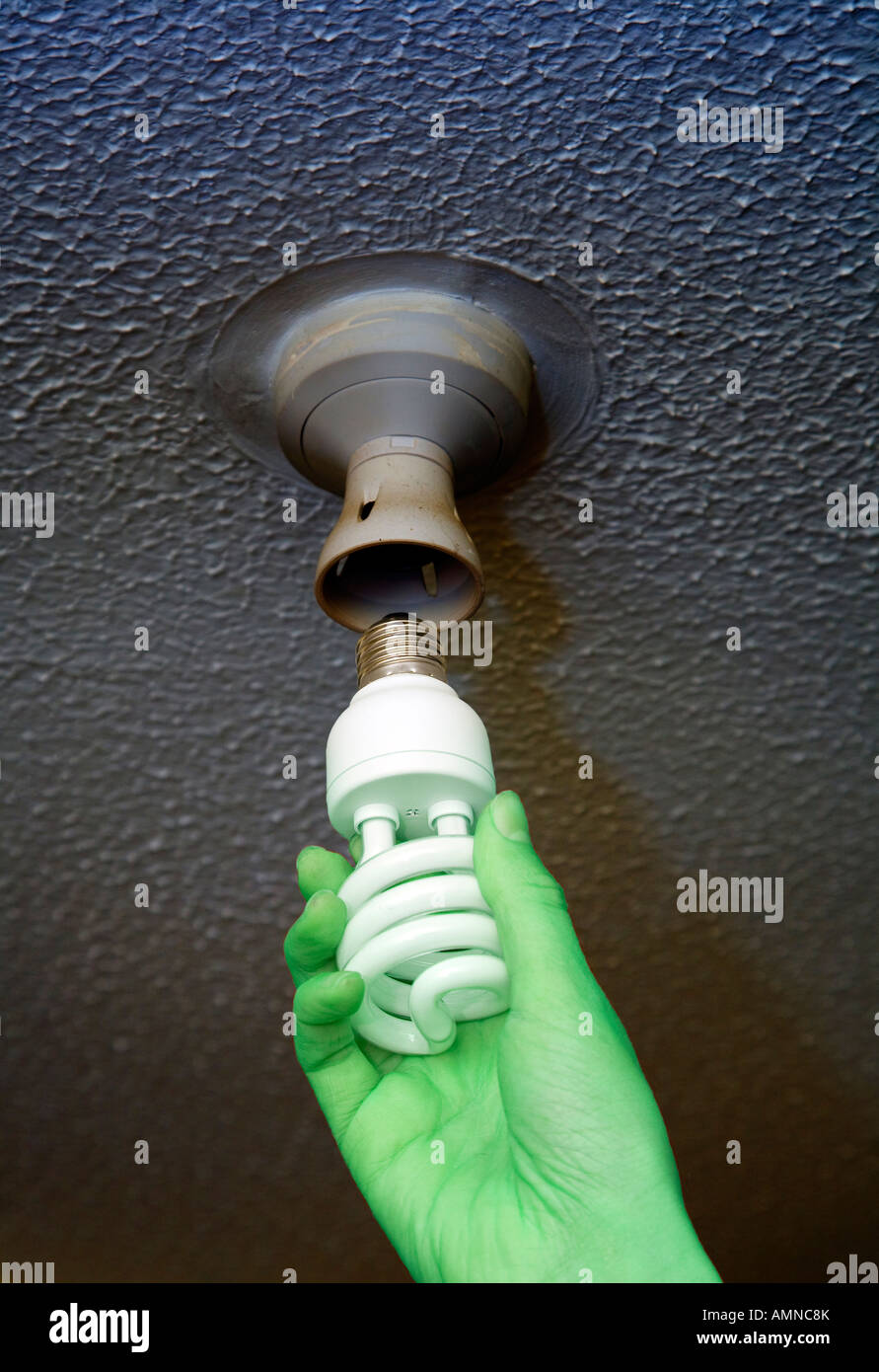 Green hand changing to an energy efficient bulb in ceiling - Stock Image