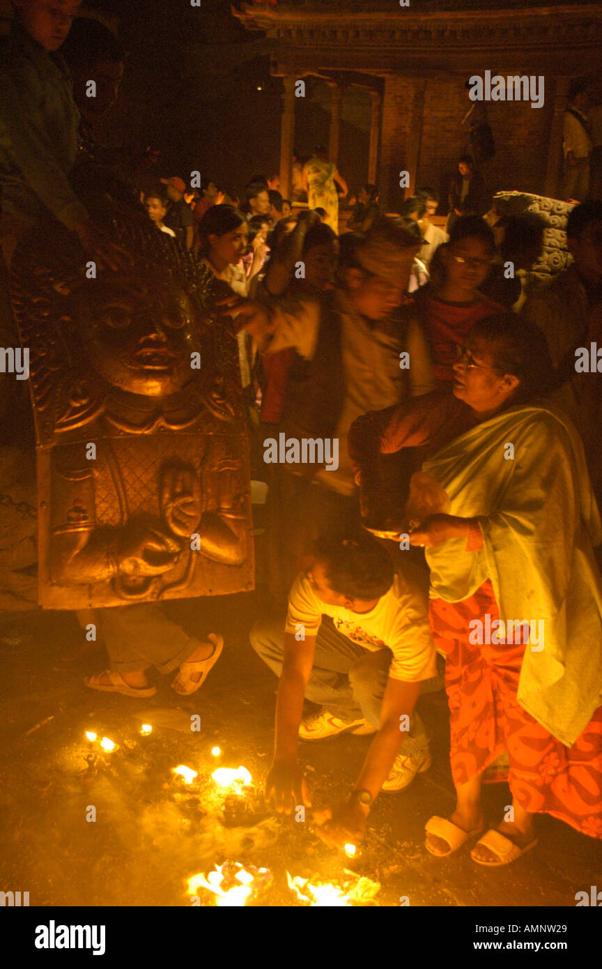 Burning butter lamps smoke and praying people at the chariot of Seto Macchendranath Kathmandu Nepal - Stock Image