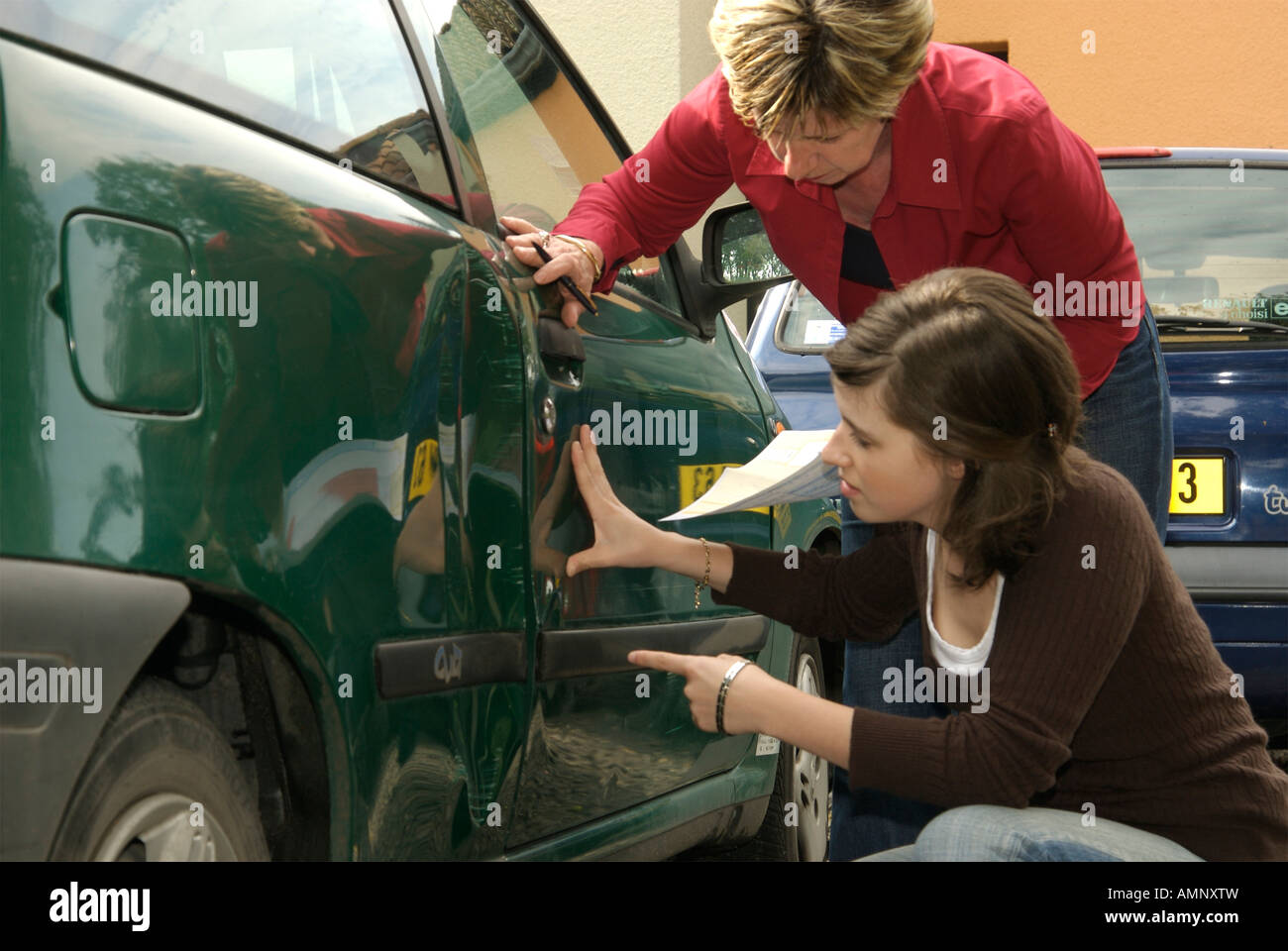 Car driver looking at the damage to her car with another driver after a road car accident in France - car insurance - Stock Image