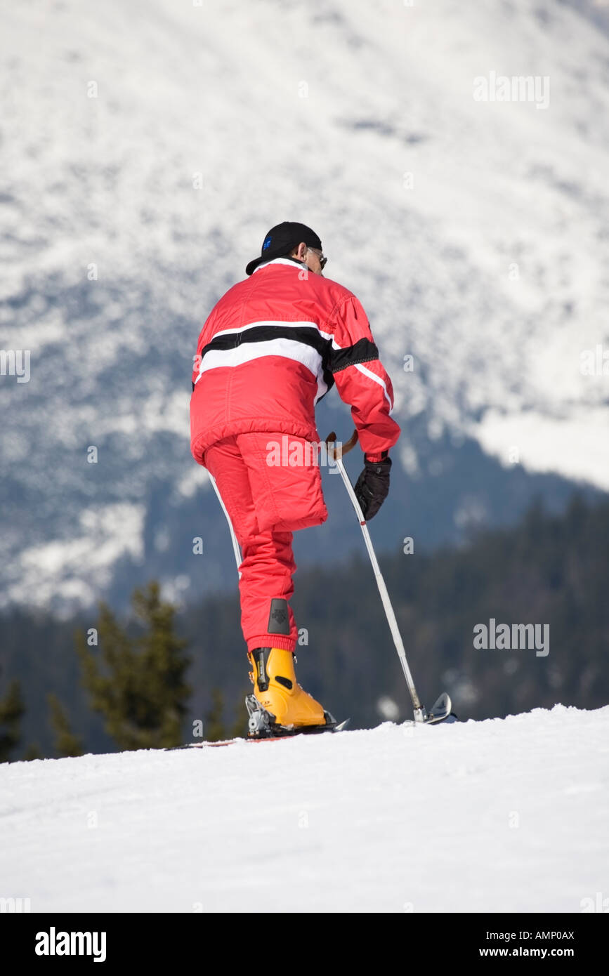One legged skier looking downhill - Stock Image