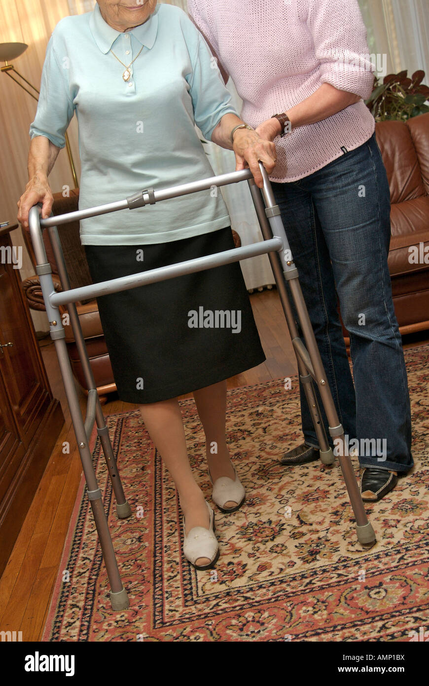 Elderly lady walking with her zimmer frame being helped by a nurse / carer - Stock Image