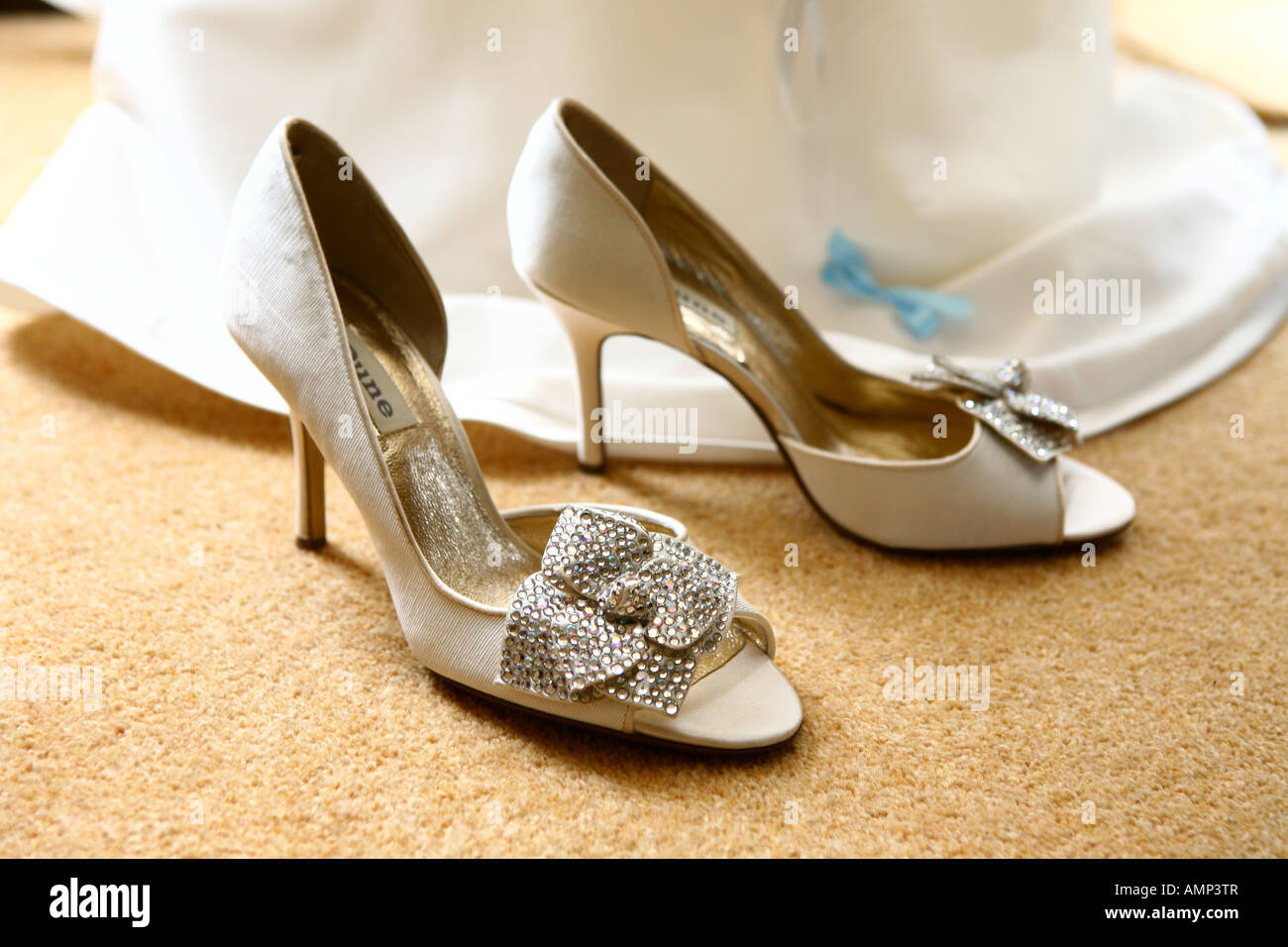 79b1649c43aaa0 Closeup of white high heeled wedding shoes with embroidered beaded  decoration and with bottom of white wedding dress behind