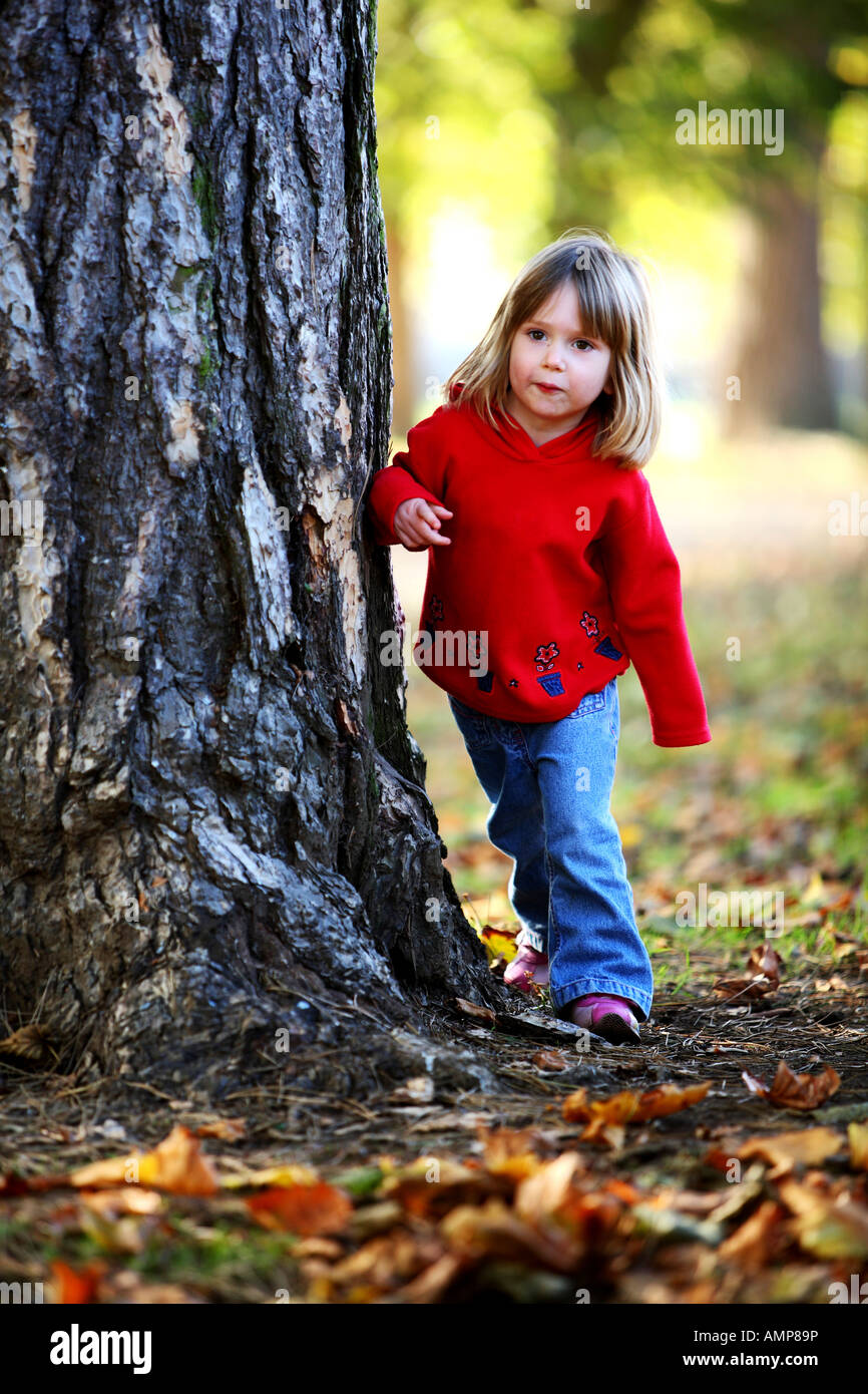 Young girl aged 4 playing hide and seek - Stock Image