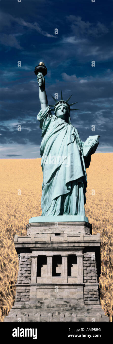 Composite image of the Statue of Liberty and pedestal against a wheat field - Stock Image