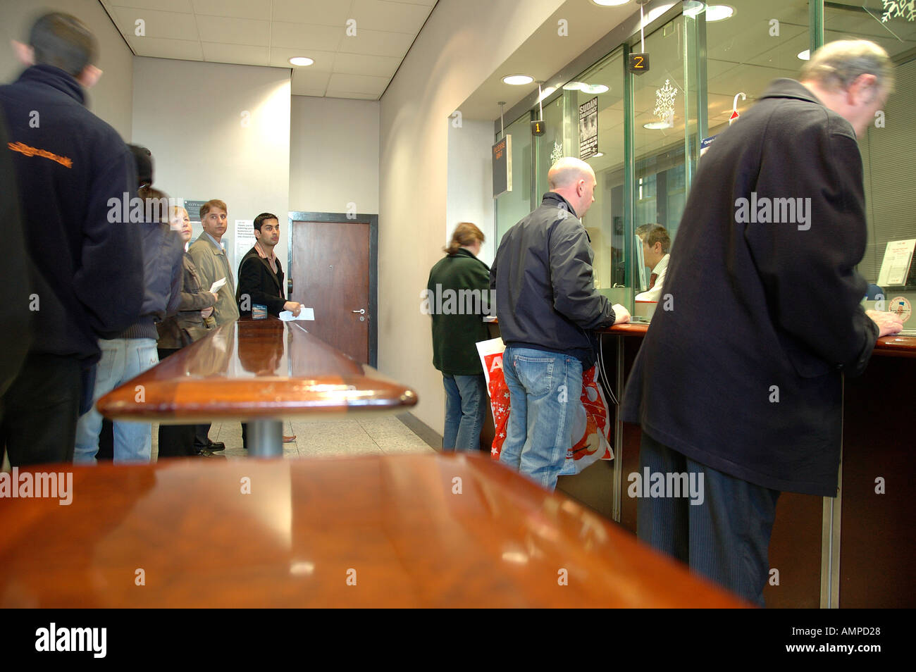 Customers queue at a branch of HSBC bank in the UK - Stock Image