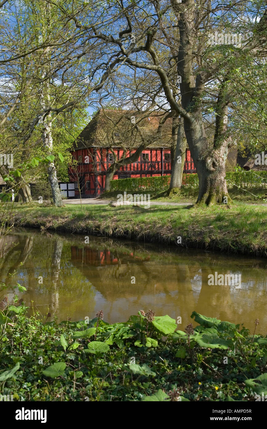 Traditional village cottage in front of a pond. The Funen Village. Odense. Denmark, Stock Photo