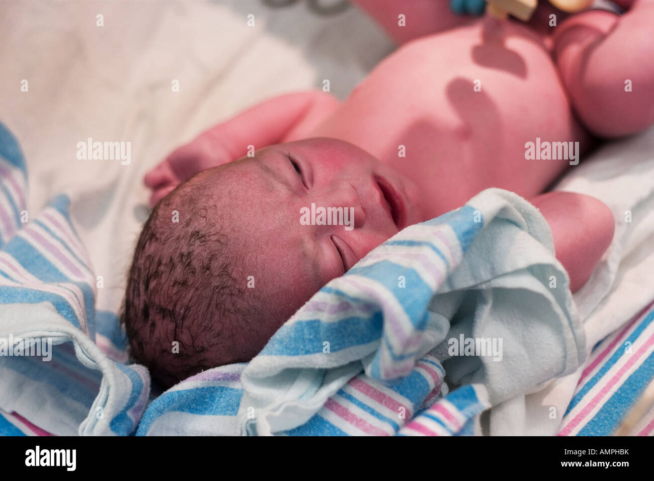 Newborn baby boy resting after being checked out in delivery room - Stock Image