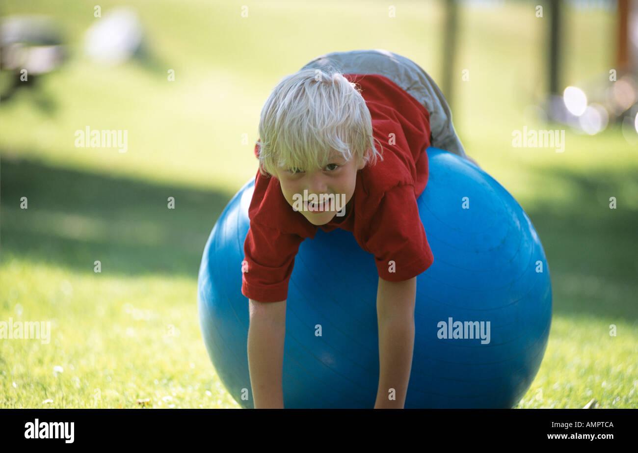 Boy (6-7) lying on big blue rubber ball, portrait Stock Photo
