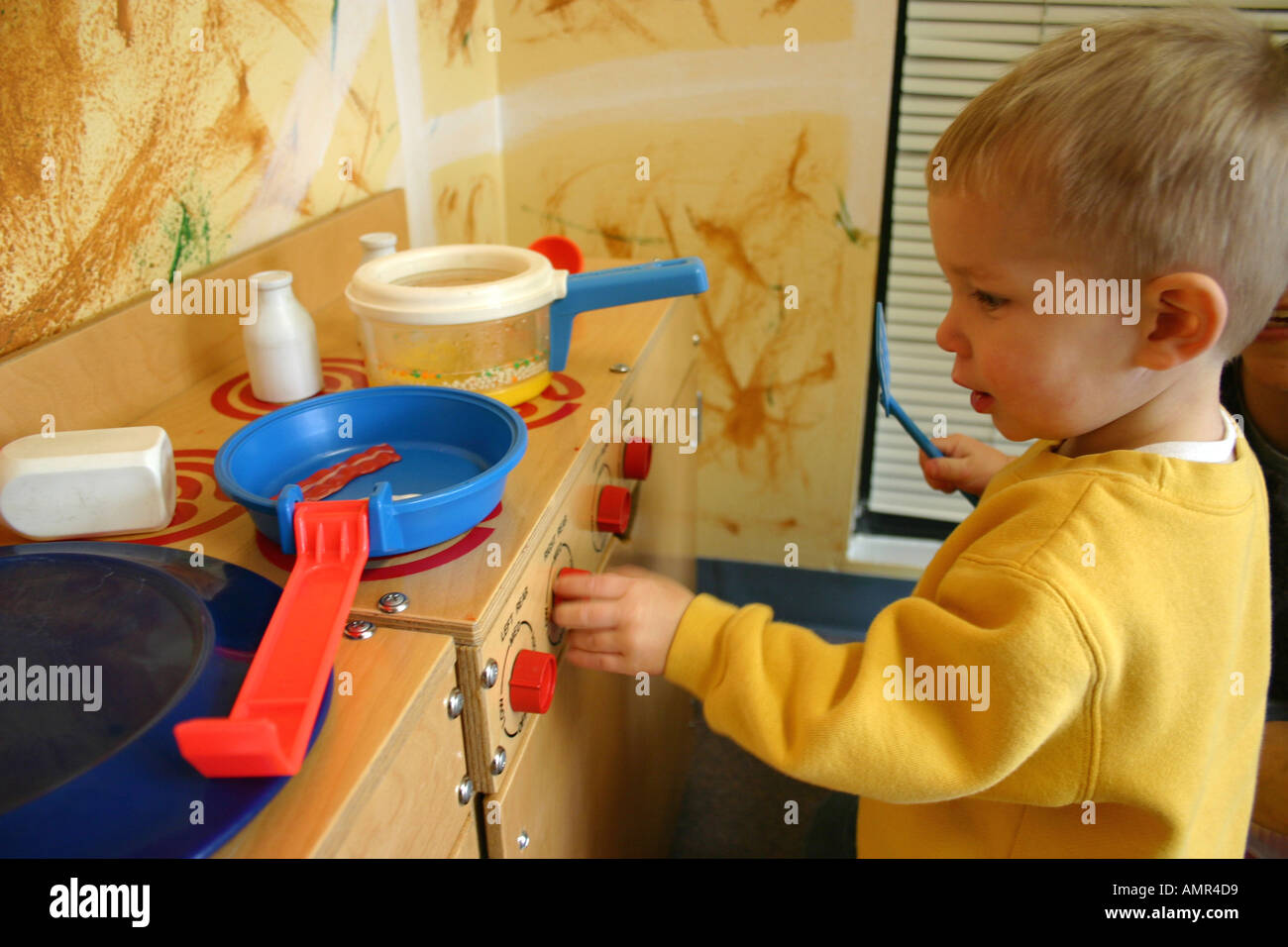 one year old engaged in pretend play cooking kitchen in ...