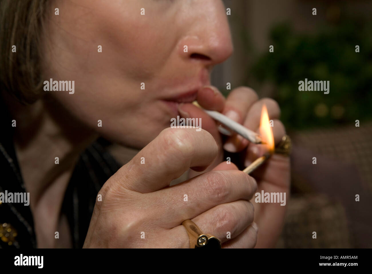 Most popular way of relaxing Woman smoking a joint or marijuana cigarette - Stock Image