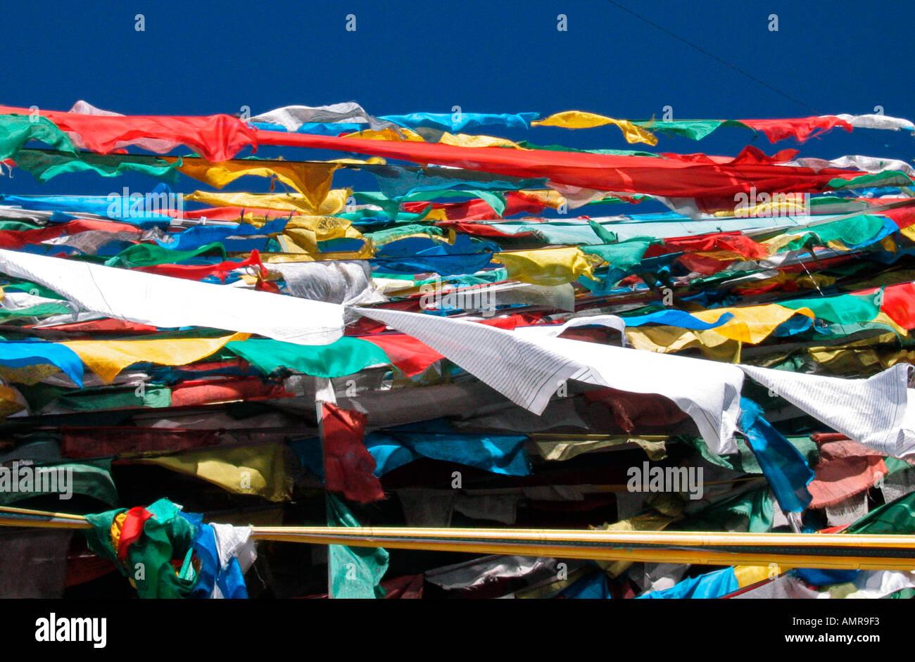 Coloured Tibetan prayer flags near 1000 Buddhas shrine on Lingkor pilgrim way Lhasa Tibet - Stock Image