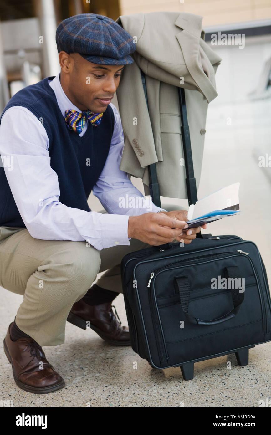 African man checking airplane ticket - Stock Image